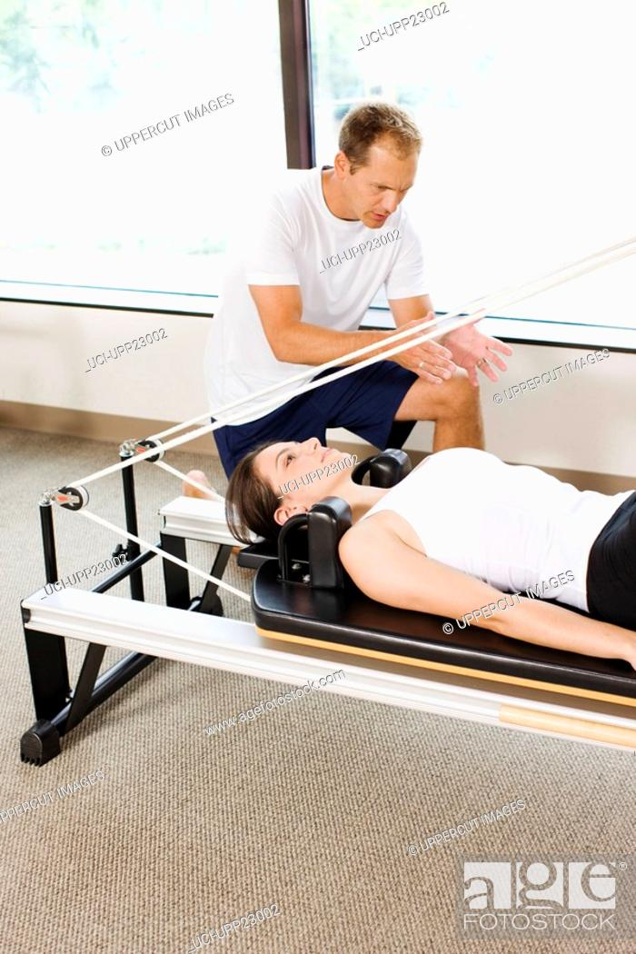 Stock Photo: Personal trainer guiding woman on pilates equipment.
