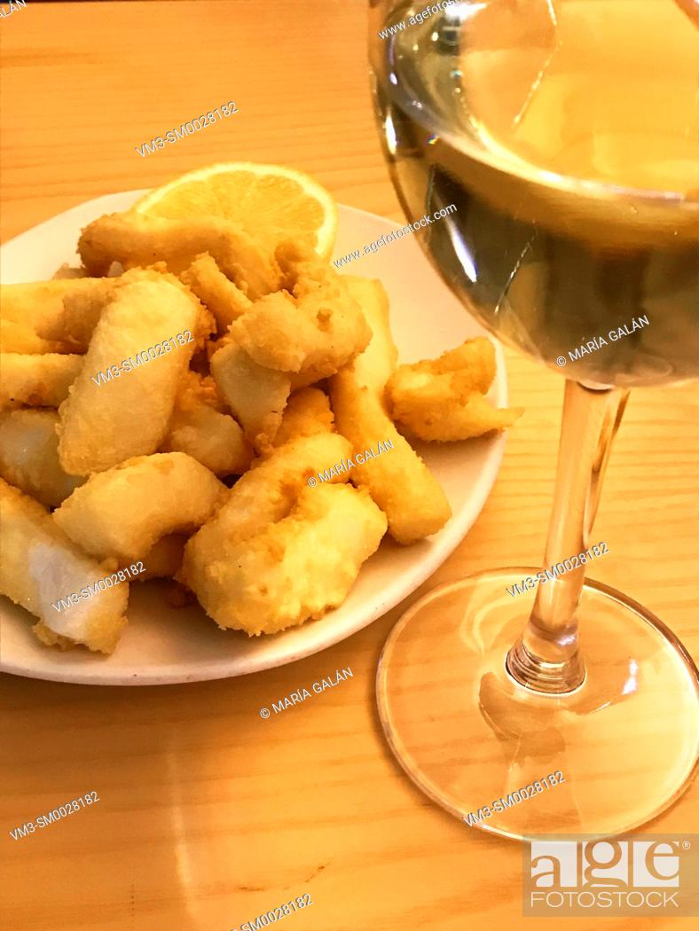 Imagen: Fried squids and glass of white wine.