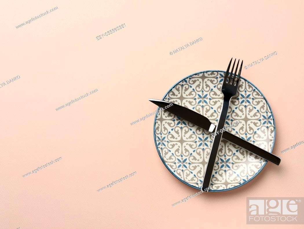 Stock Photo: round ceramic plate and crossed knife and fork on beige background, top view.