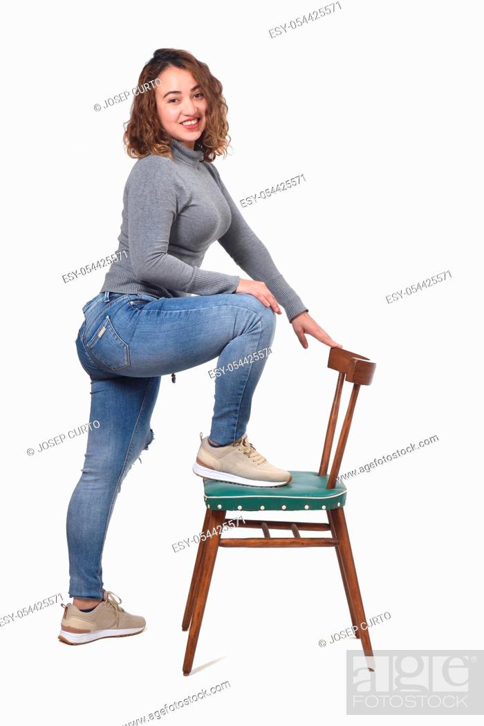 Stock Photo: woman playing with a chair in white background.