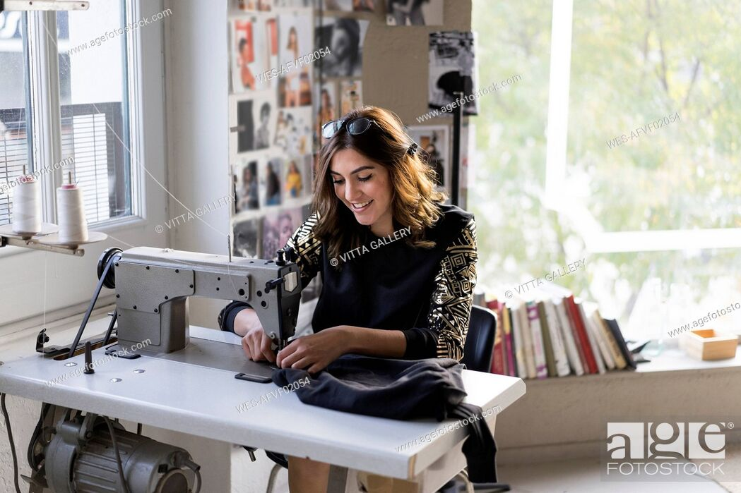 Stock Photo: Smiling young fashion designer using sewing machine in her atelier.