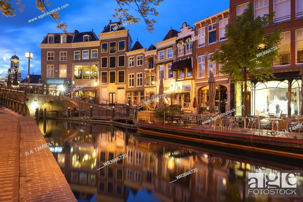 Stock Photo: Netherlands, South Holland, Leiden, Sidewalk cafe and row of townhouses reflecting in Nieuwe Rijn canal at dusk.