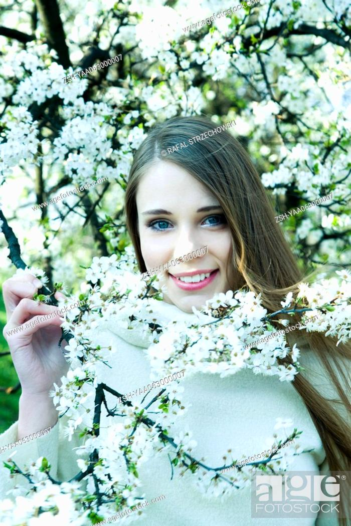 Stock Photo: Teenage girl standing among flowering tree, smiling at camera, portrait.
