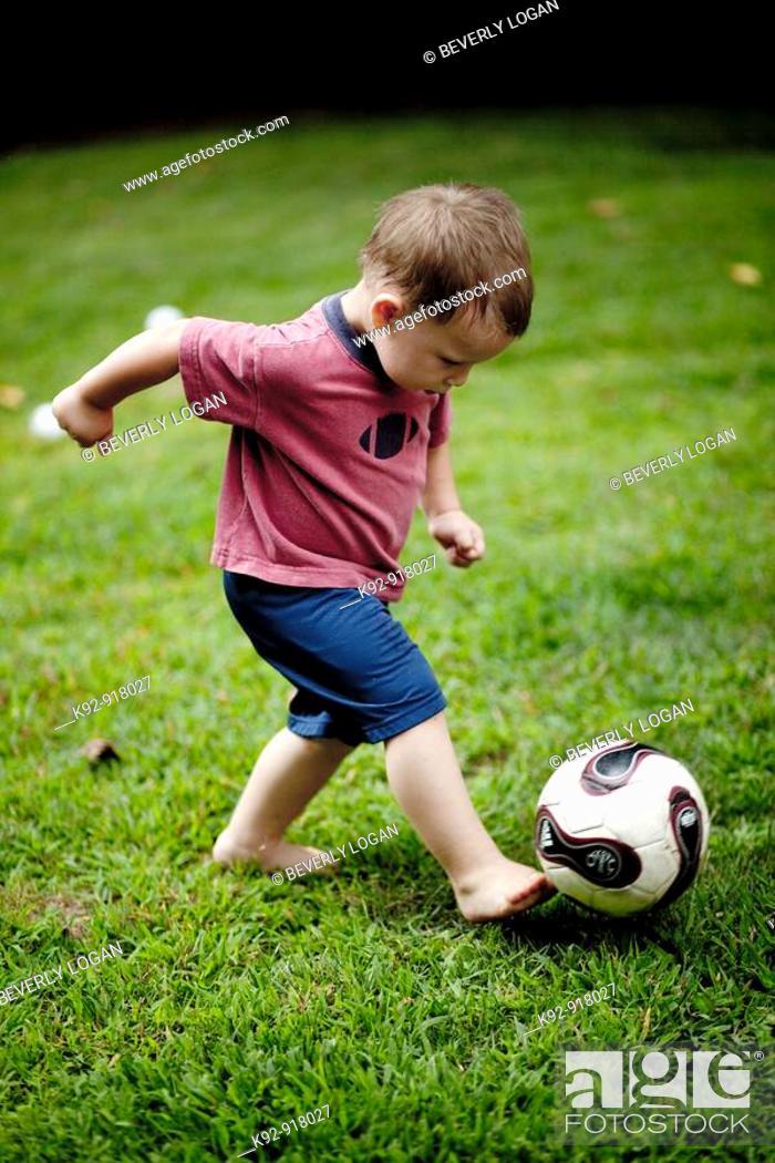 Stock Photo: Boy kicking a soccer ball.