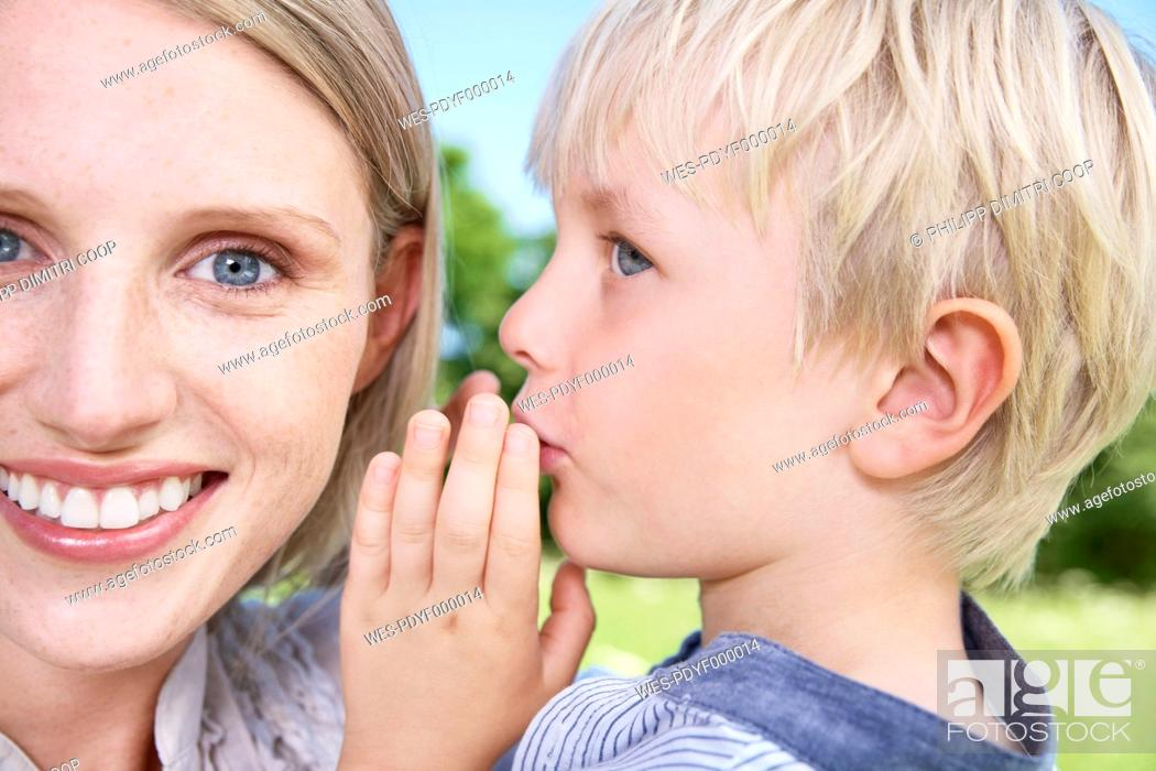 Stock Photo: Germany, Cologne, Son whispering to his mother.