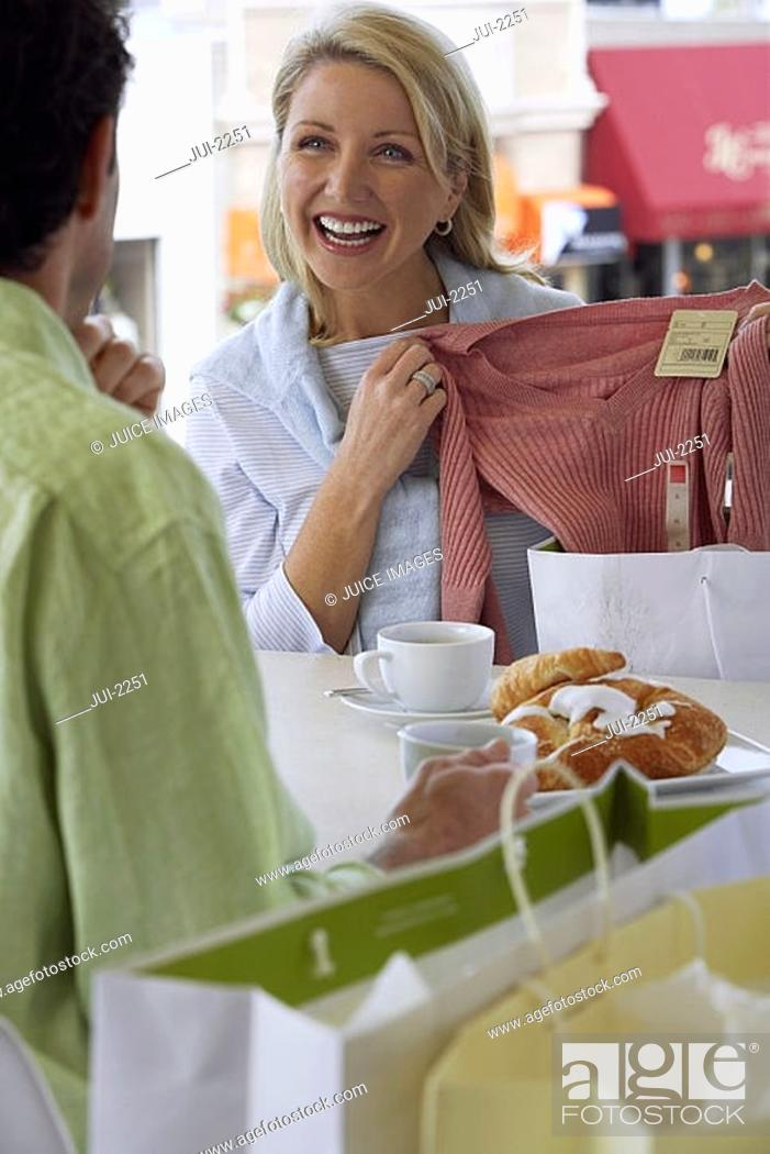 Stock Photo: Couple sitting at cafe table, blonde woman showing man new top, laughing.
