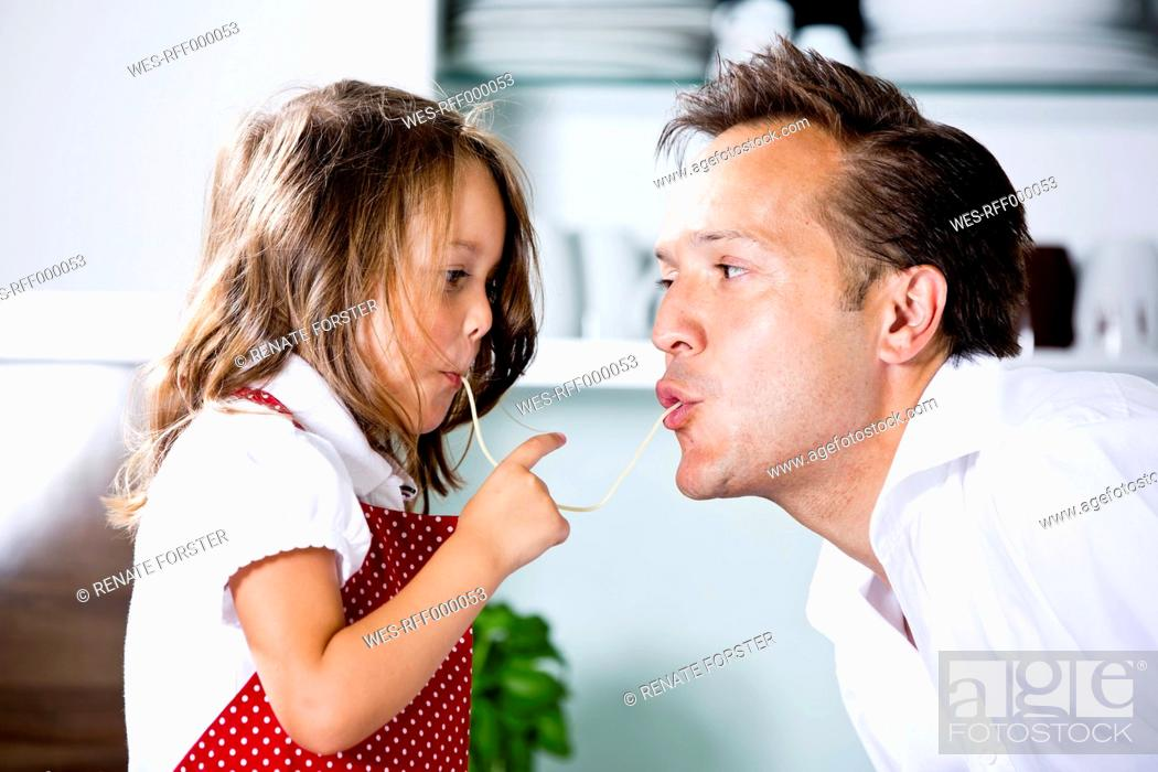 Stock Photo: Germany, Daughter eating noodles with father in kitchen.