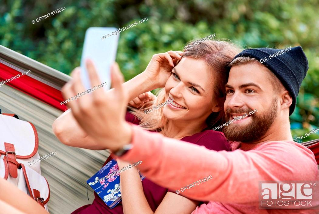 Stock Photo: Couple in hammock taking selfie smiling, Krakow, Malopolskie, Poland, Europe.