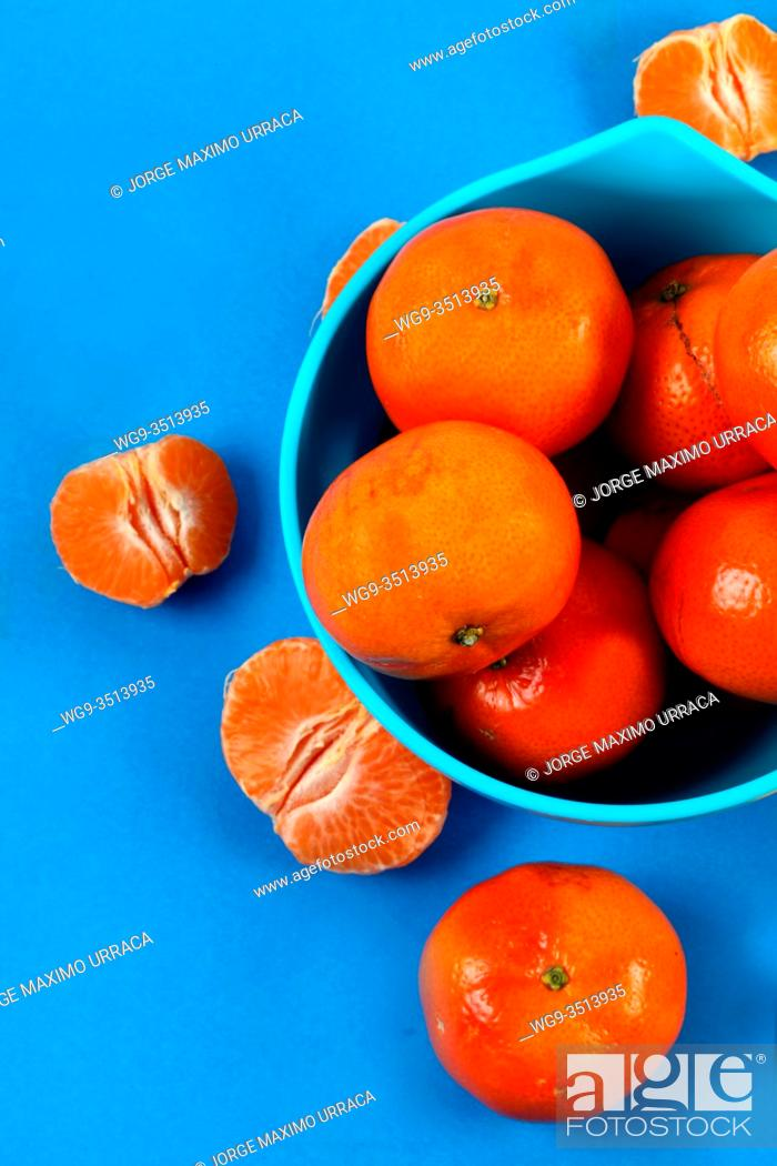 Stock Photo: Blue bowl with tangerines in blue background.