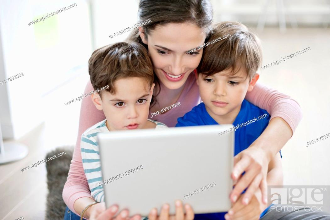Stock Photo: Woman showing a digital tablet to their children.