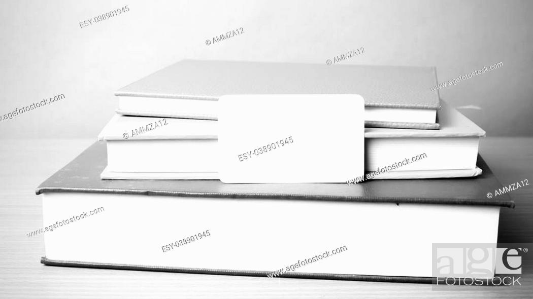 Stock Photo: stack of book and business card on wood background black and white color tone style.
