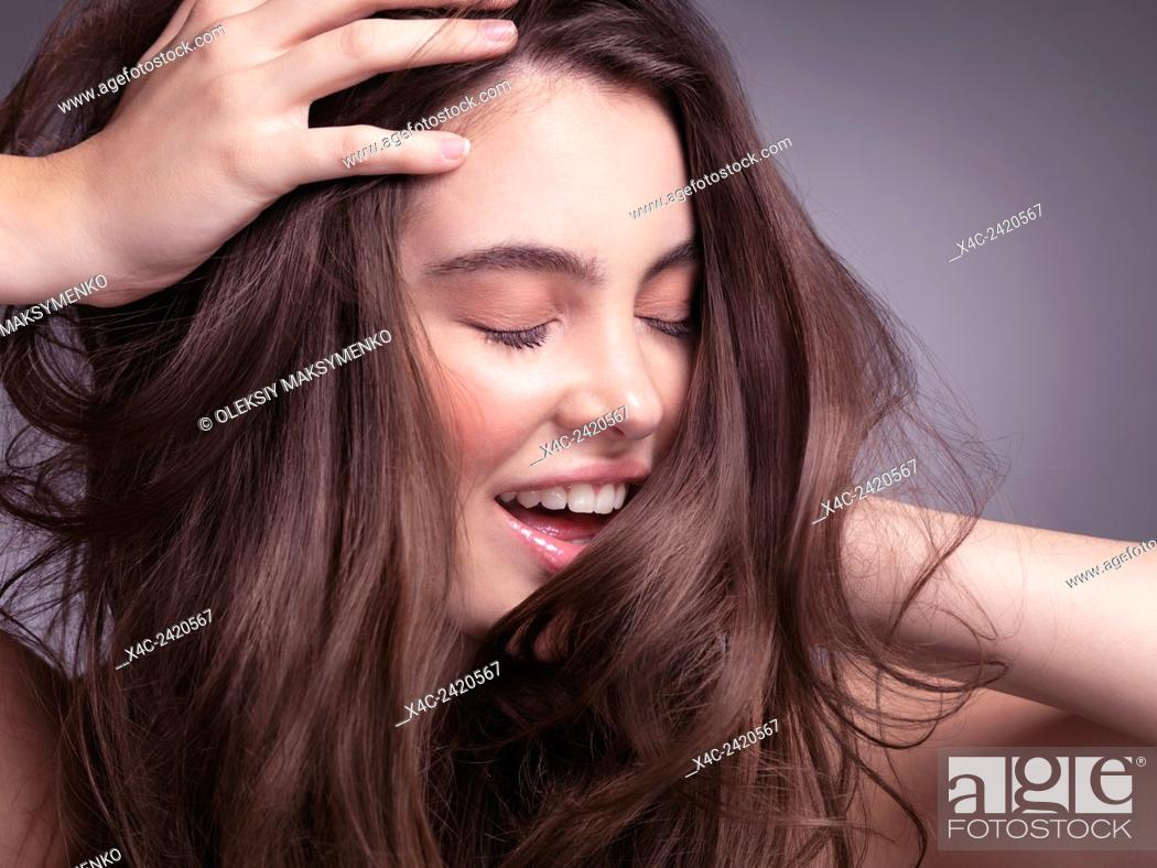 Stock Photo: Closeup portrait of a smiling pretty young woman with long brown hair.