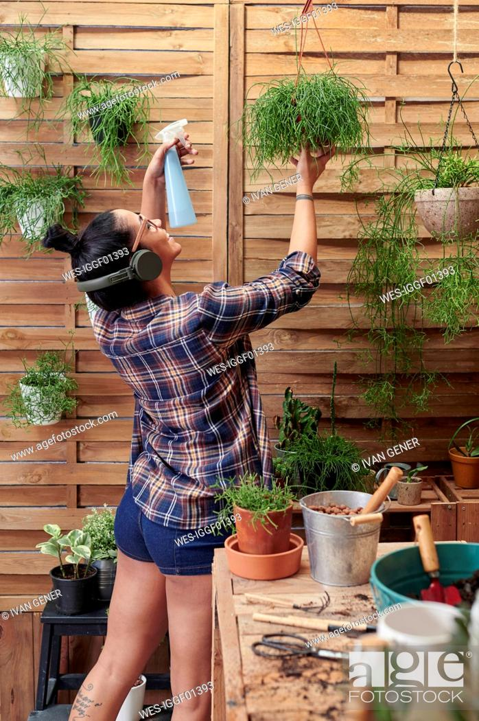 Stock Photo: Happy woman spraying water on plants on her terrace while listening to music.