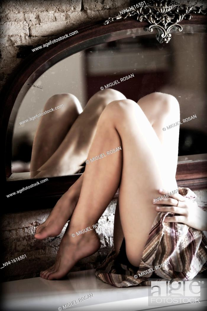 Stock Photo: Bent legs of a young woman lying down and reflected in a mirror.