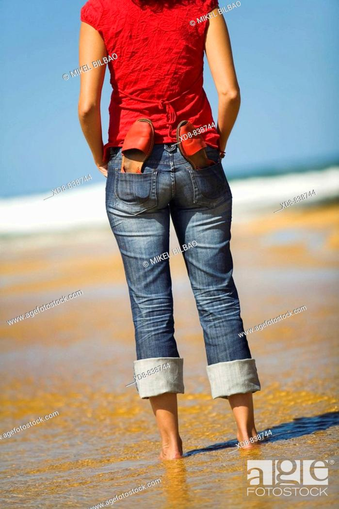 Stock Photo: Portrait of a young woman with a pair of sandals on the beach.