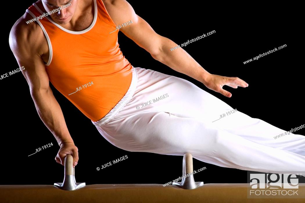 Stock Photo: Male gymnast performing on pommel horse, close-up.