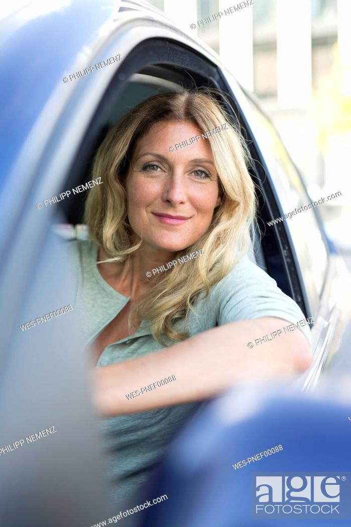 Stock Photo: Portrait of smiling woman in car.