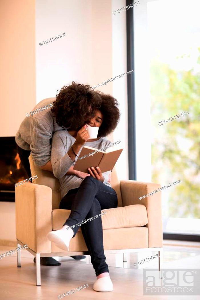 Stock Photo: Young beautiful multiethnic couple hugging in front of fireplace at home when reading a book at autumn day.