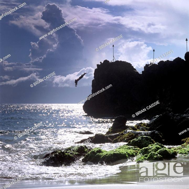 Stock Photo: A silhouetted person diving off a cliff, Maui, Hawaii.