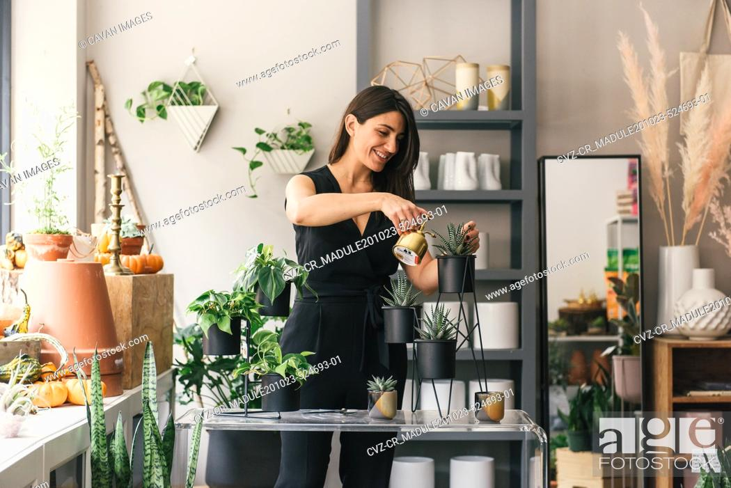 Stock Photo: Smiling flower shop owner waters newly planted succulent display.