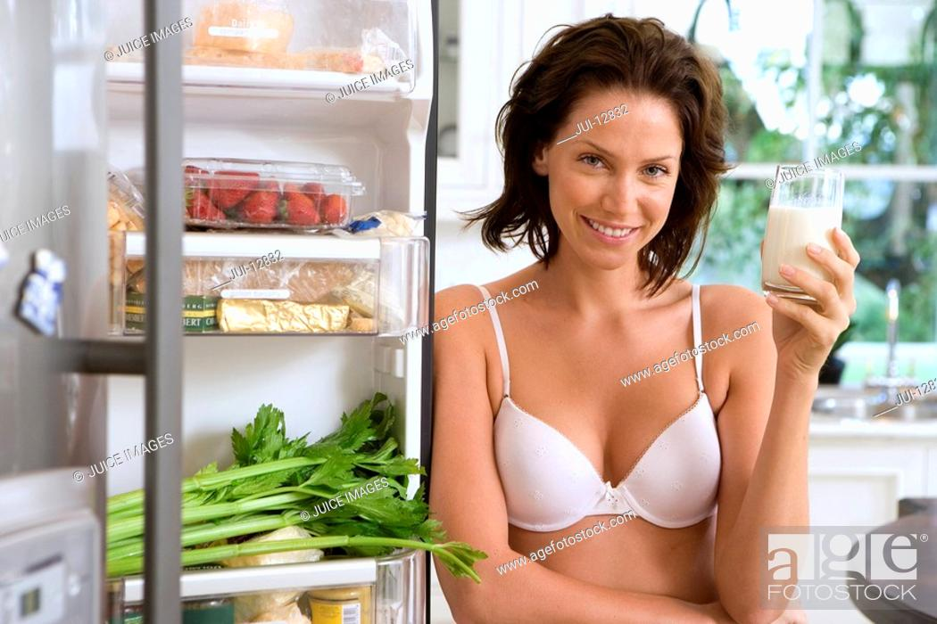 Stock Photo: Young woman in underwear with drink by open door of fridge, smiling, portrait.