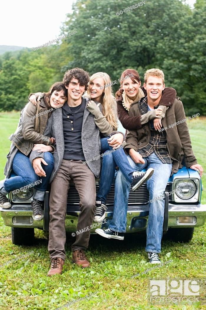 Stock Photo: Friends sitting on a car.