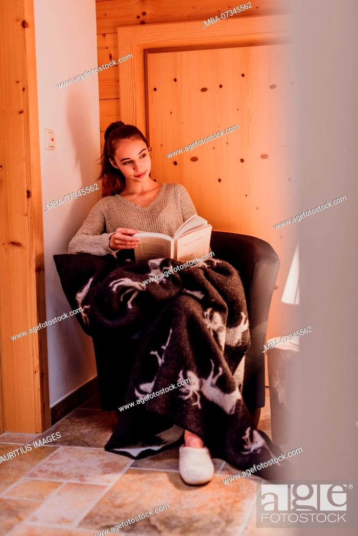 Stock Photo: young woman wrapped in a blanket, reading a book, lamp, warm light.