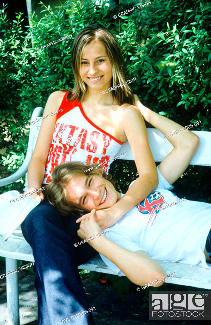 Stock Photo: Portrait of young couple together on a park bench.