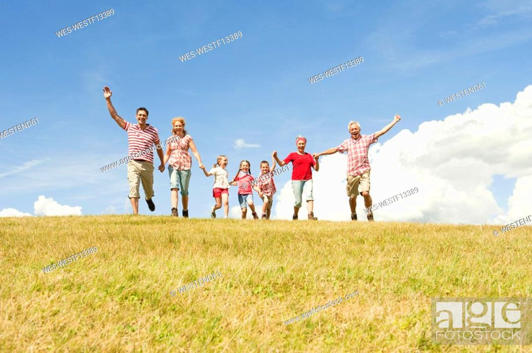 Stock Photo: Italy, Seiseralm, Family walking in field, cheering.