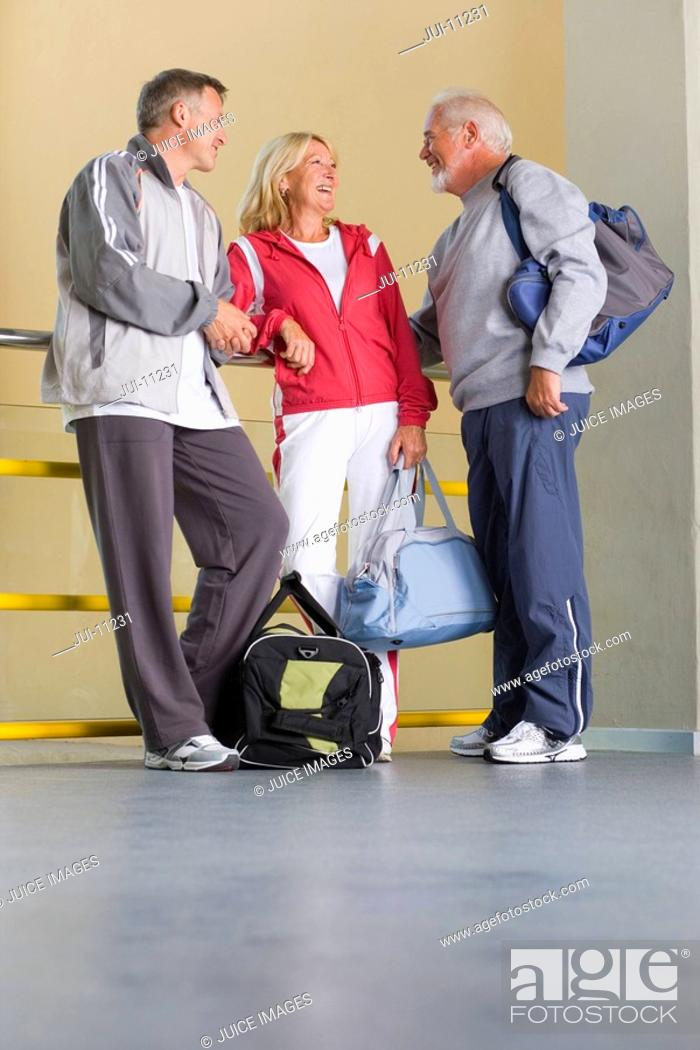 Stock Photo: Senior couple in conversation with man, all with gym bags, low angle view.