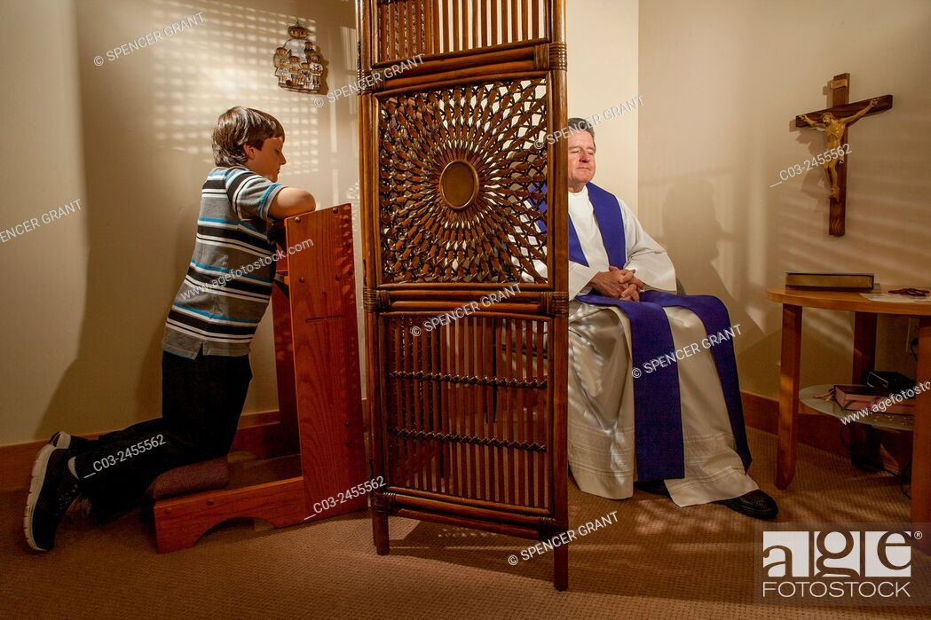 Stock Photo: Hidden by a screen, a priest hears confession from a kneeling boy parishioner at a Laguna Niguel, CA, Catholic church. Note vestments. MODEL RELEASE.