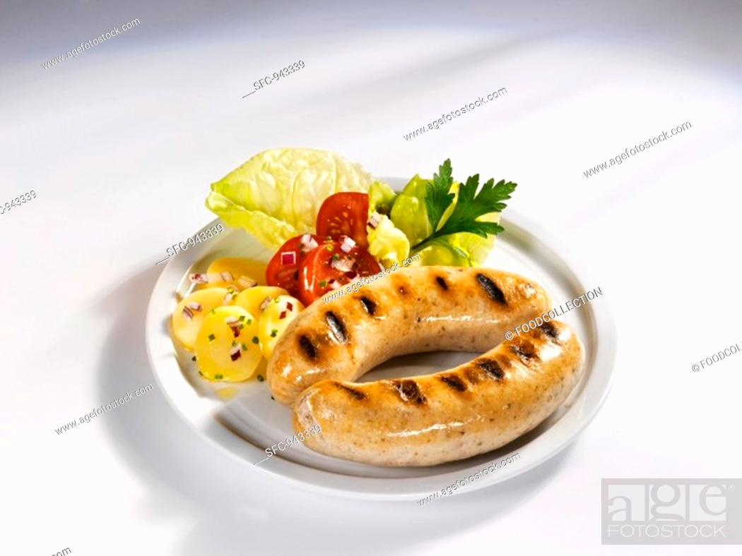 Stock Photo: Two grilled sausages with potato and tomato salad.