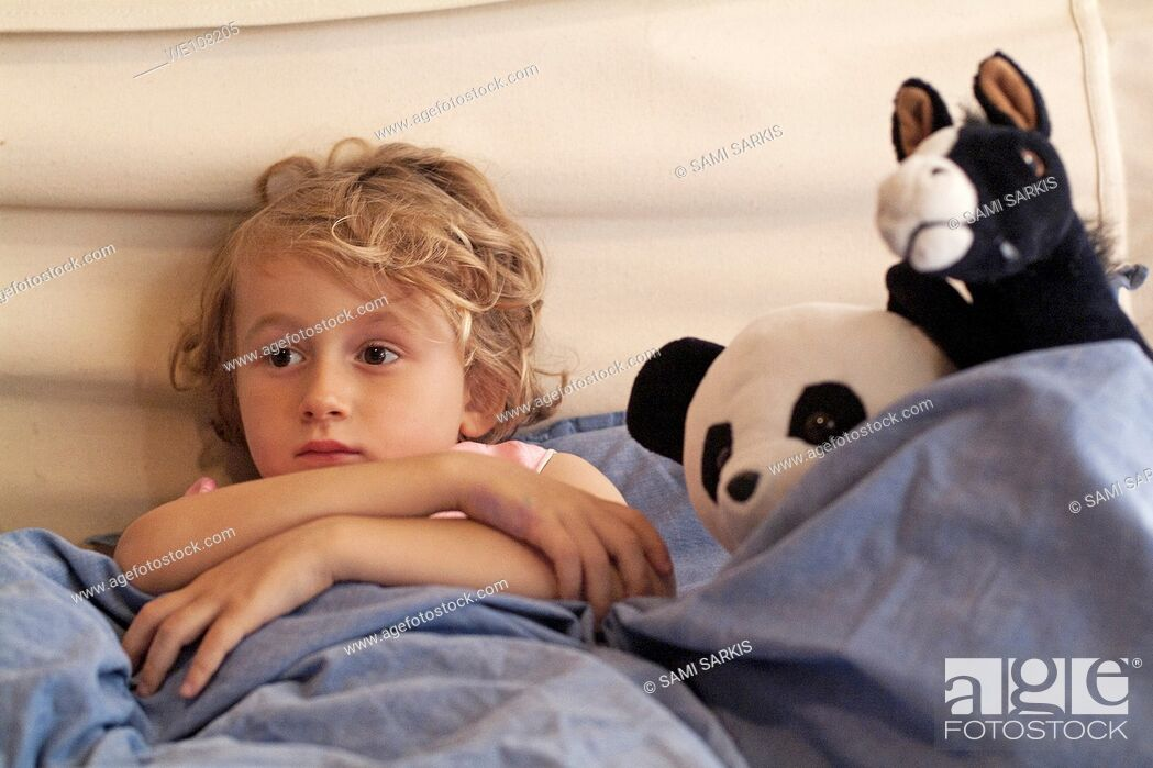 Stock Photo: Little girl watching TV in bed, surrounded by her favourite stuffed animals.