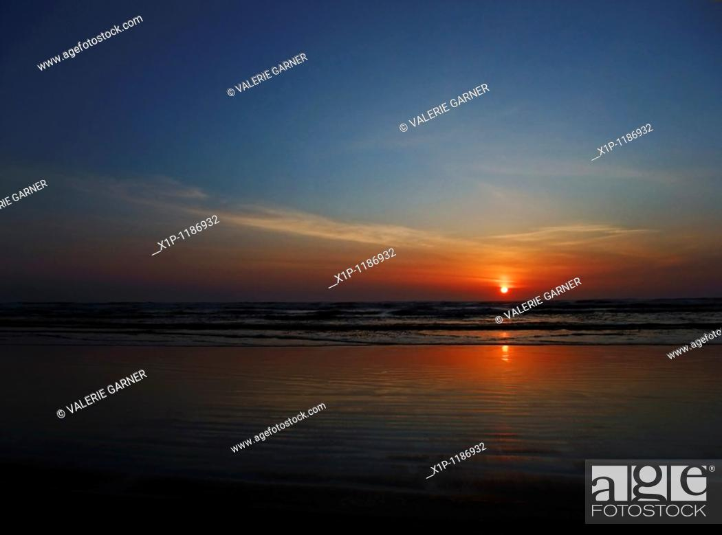 Stock Photo: This stock photo is a stunning sunset at the beach as the sun is just about to dip over the horizon Horizontal format this conveys of concepts of vacation.