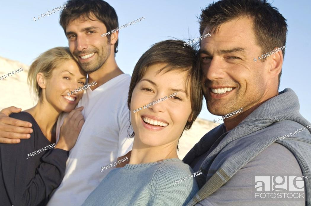 Stock Photo: 2 smiling couples on the beach.