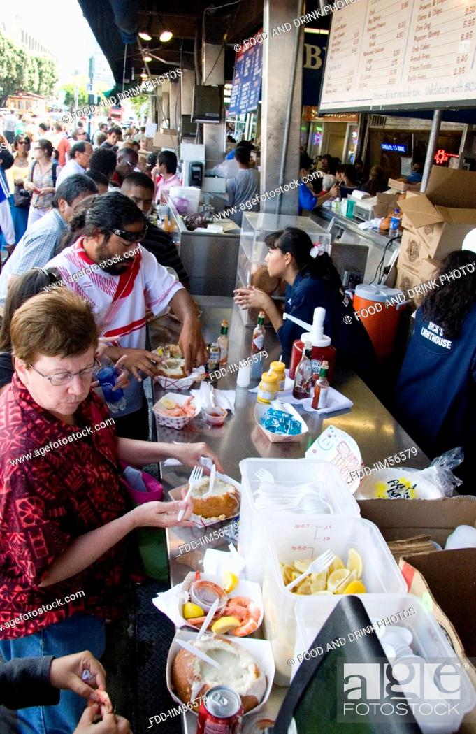 Stock Photo: Tourists eating seafood at a standup sidewalk restaurant at Fisherman's Wharf in San Francisco, California, USA.