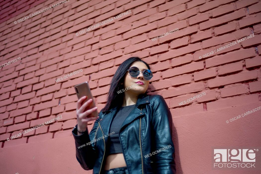Stock Photo: Portrait of young woman with smartphone wearing sunglasses and black leather jacket.