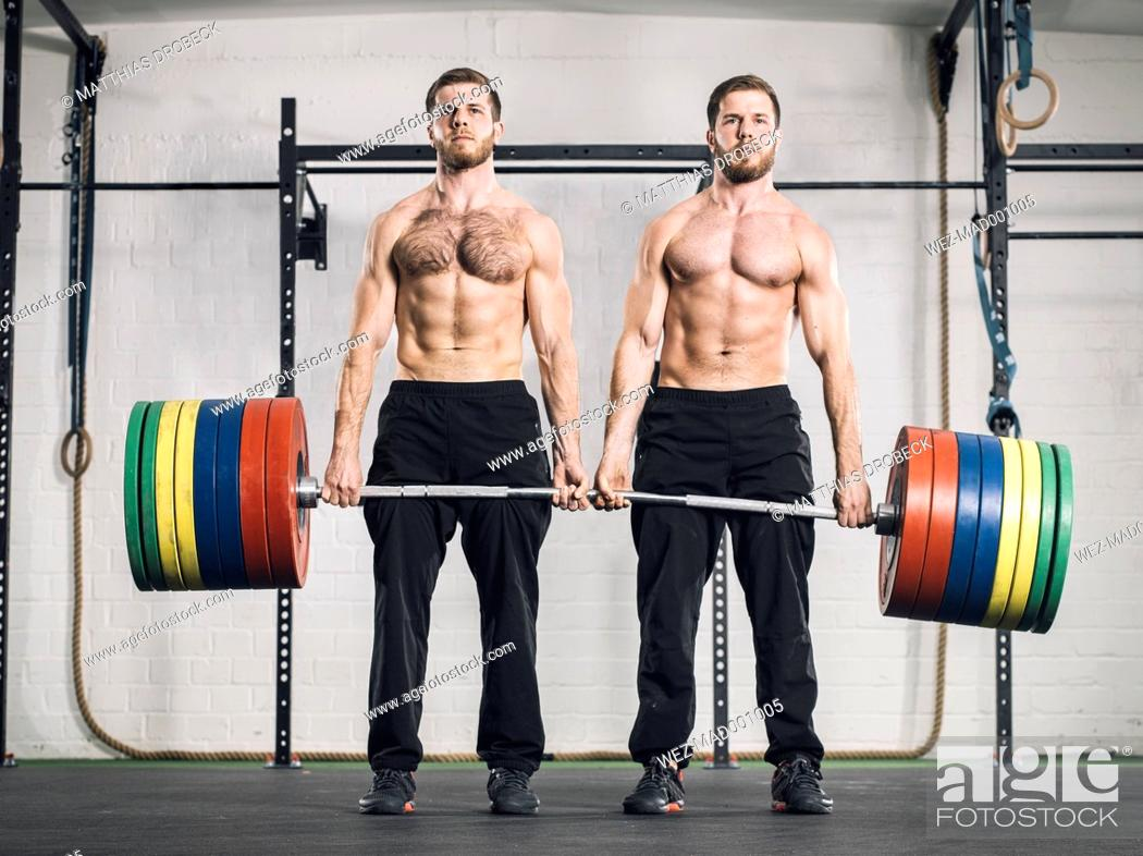 Stock Photo: Twin brothers weightlifting in gym.