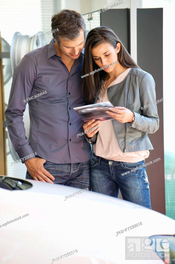 Stock Photo: Happy couple looking at car catalog in showroom.