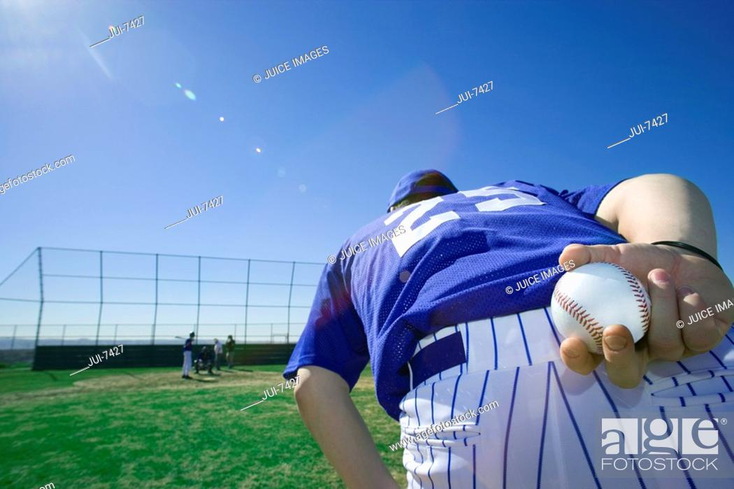 Stock Photo: Baseball pitcher, in blue uniform, preparing to throw ball during competitive game, holding ball behind back, close-up, rear view lens flare.