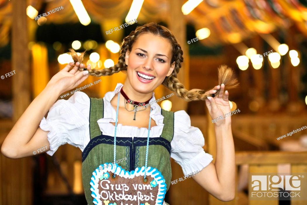 Stock Photo: Young woman holding up her pigtails at Oktoberfest, Munich, Germany.