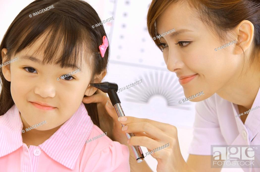 Stock Photo: Young nurse making body care for little girl.