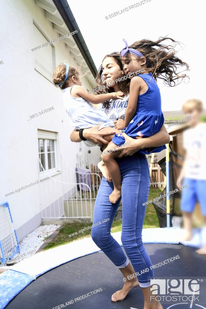 Stock Photo: Young girl jumping on trampoline with her little sister in arms.