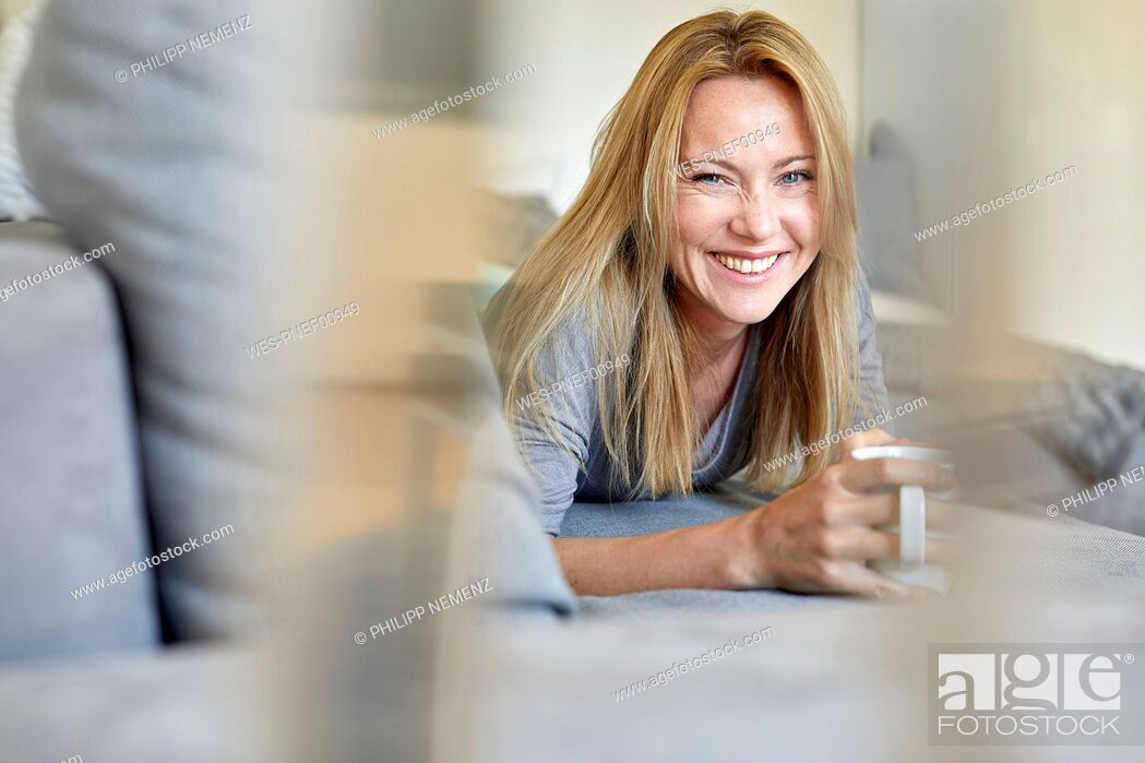 Stock Photo: Laughing young woman relaxing on couch, drinking coffee.