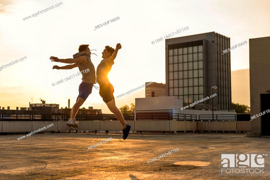 Stock Photo: Friends jumping for joy at sunset.