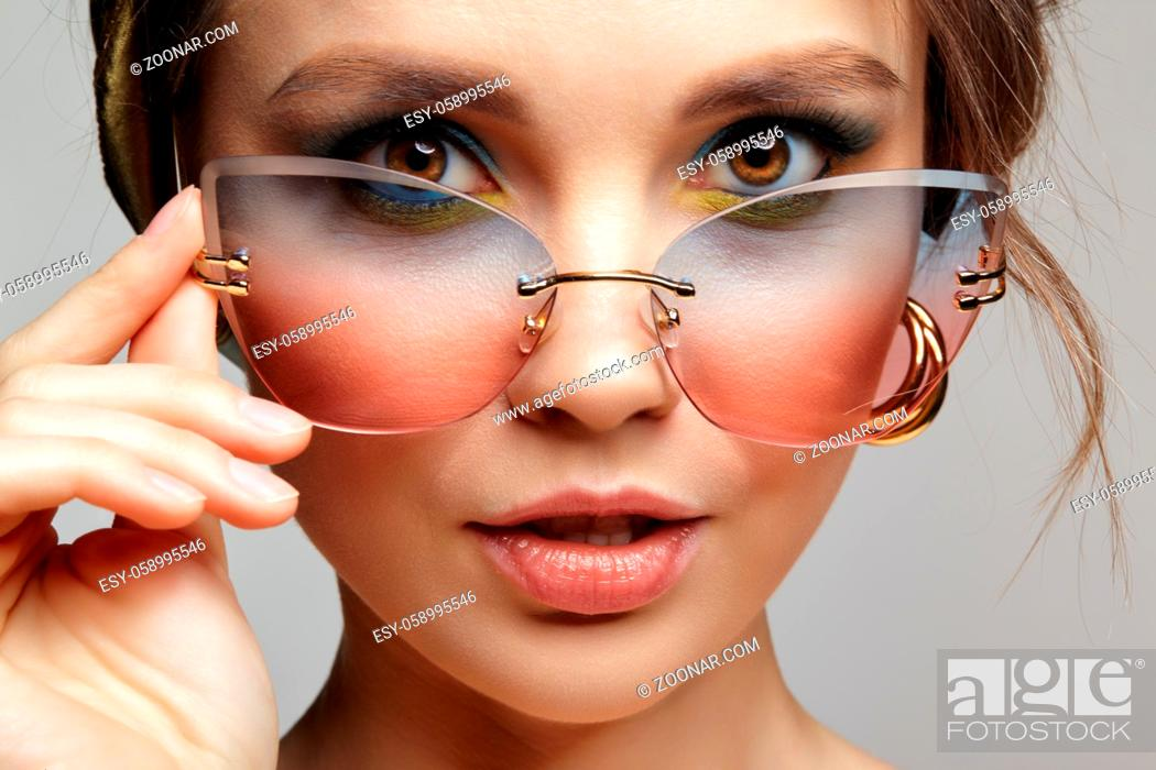 Stock Photo: Portrait of young woman with sunglasses in hand. Female in headscarf is looking at the camera through glassess. Makeup with blue eyeshadow and yellow eyeliner.