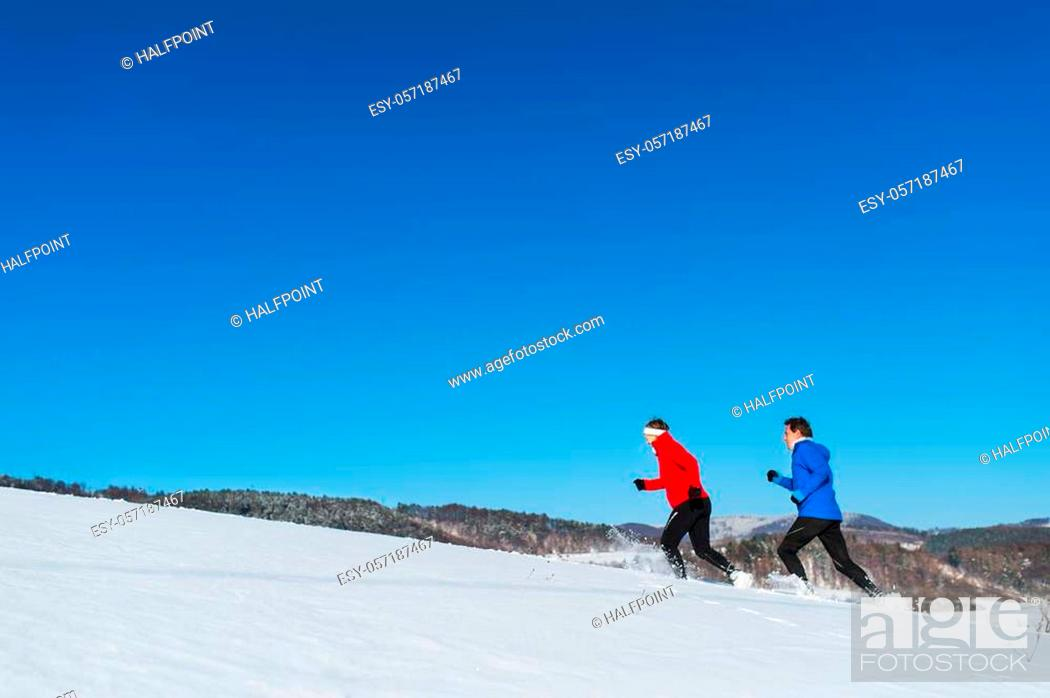 Imagen: A side view of happy senior couple jogging in snowy winter nature. A copy space.