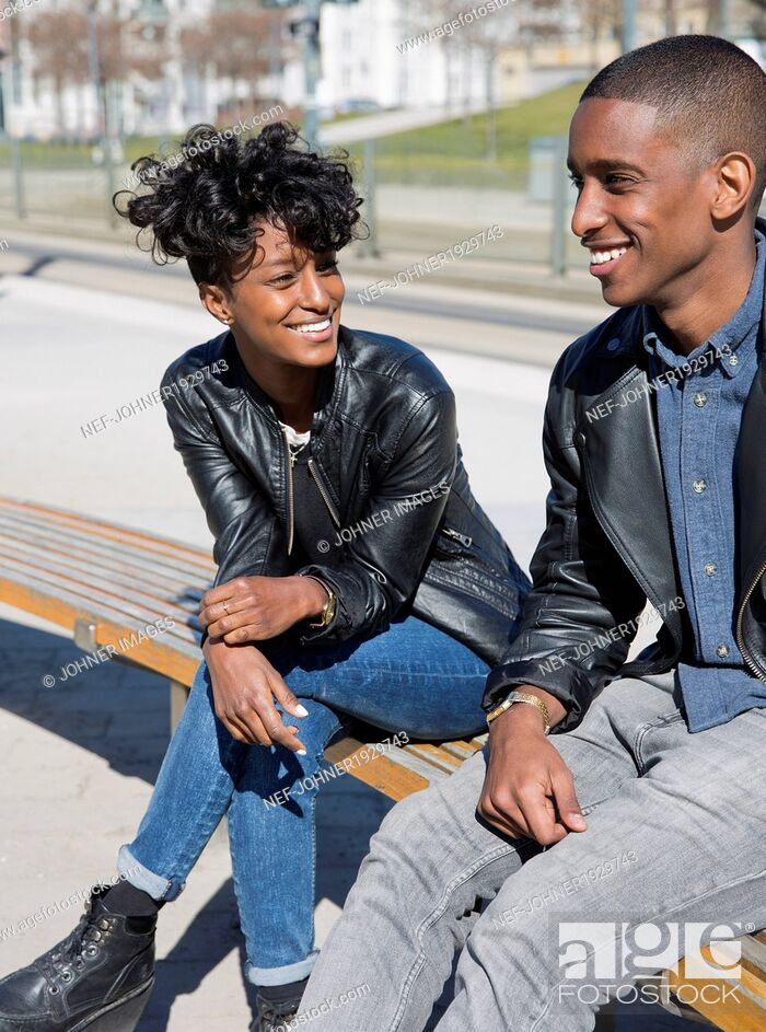 Stock Photo: Smiling young couple sitting on bench.