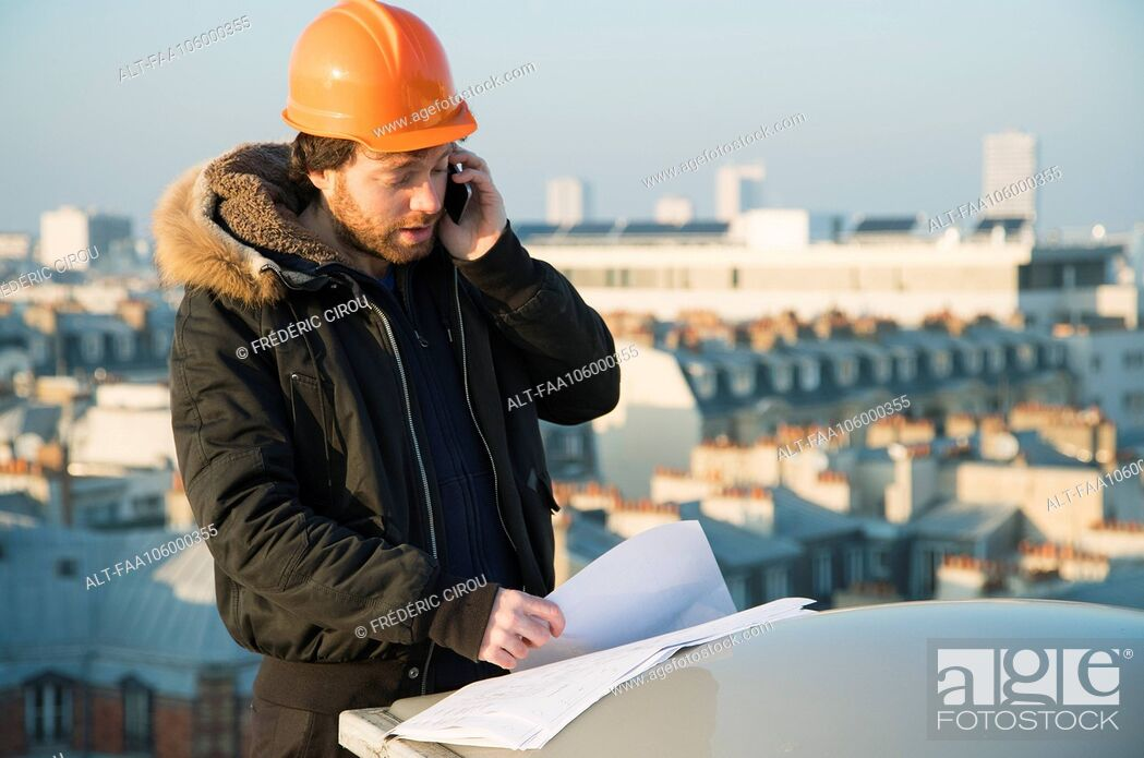 Stock Photo: Construction supervisor studying blueprints and talking on cell phone.