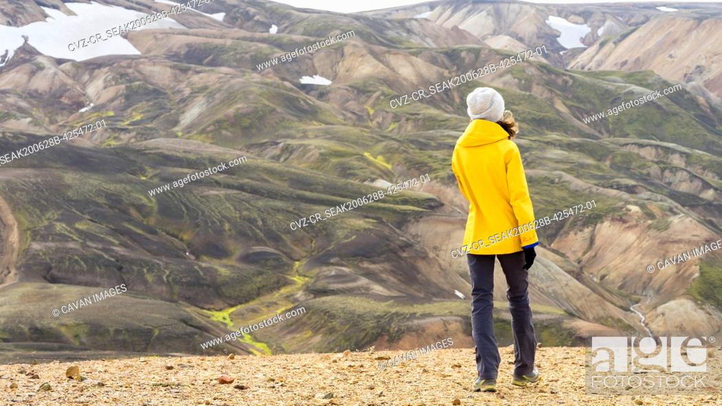 Stock Photo: Bright woman hiker walking in Iceland's highlands mossy hills.